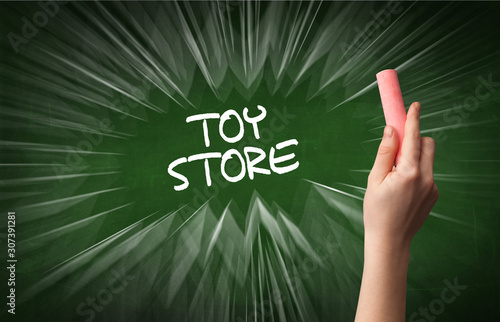 Hand drawing TOY STORE inscription with white chalk on blackboard, online shopping concept