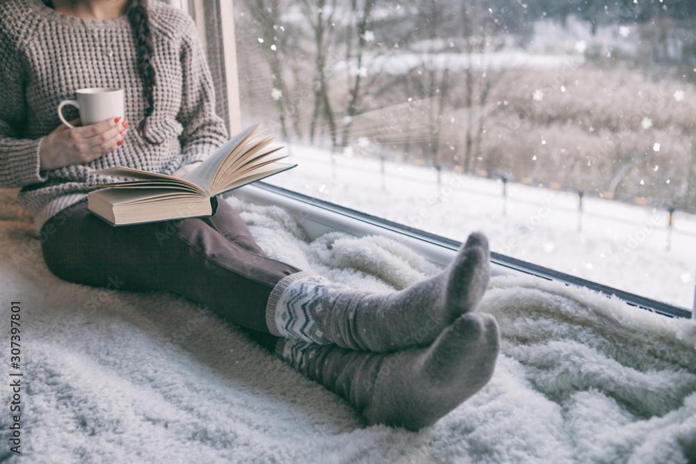 Fototapeta Woman sitting by the window reading book drinking coffee. Winter snowing landscape outside