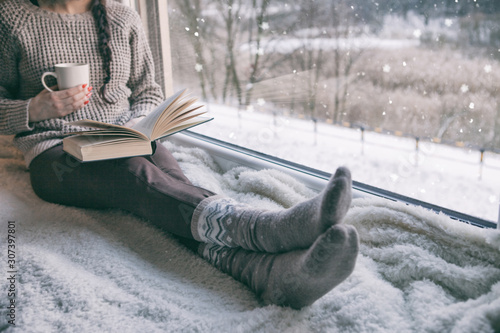 Fototapeta Woman sitting by the window reading book drinking coffee. Winter snowing landscape outside  obraz