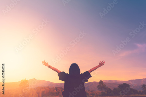 Fotografiet Copy space of woman rise hand up on top of mountain and sunset sky abstract background
