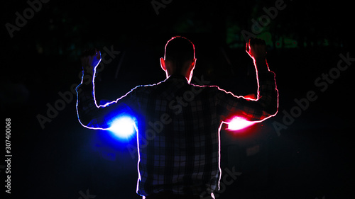 Fotografija silhouette of  a male  criminal suspect with hands up during night pursuit in fr