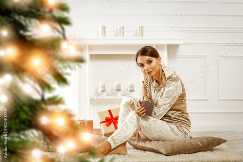Foto op Plexiglas Hoogte schaal Beautiful young brunette in golden Christmas fashionable sweat suit.Christmas tree and presents.Interior of luxury apartment with ecological fireplace.Decorating candles and Christmas lights.Copy spac