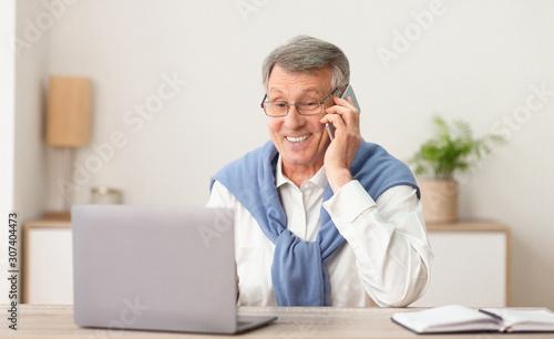 Elderly Man Talking On Phone Working On Laptop At Workplace