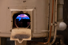 Fragment Of An Old White Gas Heating Boiler. There Are Metal Fittings And Pipes. An Open Window Shows A Blue Flame On The Burner. Background.