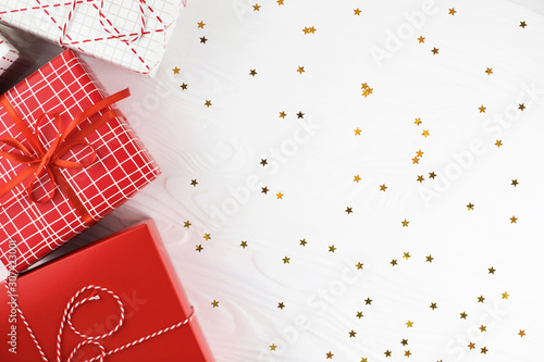 Fototapeta Festive gift boxes on white background with golden star confetti. Flat lay style. obraz na płótnie