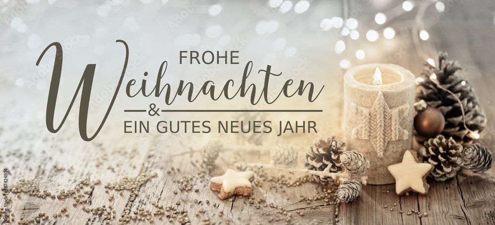 Fototapeta Christmas greeting card german text - Merry Christmas and happy new year - White burning candle with natural decoration on rustic light wood