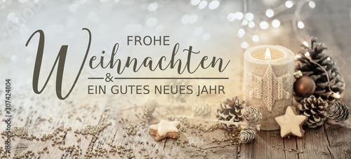 Christmas greeting card german text - Merry Christmas and happy new year - White burning candle with natural decoration on rustic light wood - 307424804