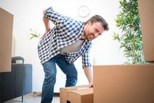 Man Feeling Back Ache Cramp Lifting Heavy Boxes