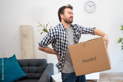 Pain in back. Young man suffering while lifting a cardboard box