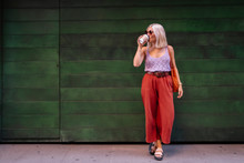 Happy Blonde Female In Stylish Outfit Enjoying Fresh Fruit Beverage While Standing On Green Wooden Wall On The Street