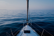 View From Deck Of Sailboat Flowing On Calmed Water Of Sea At Dusk