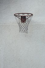 Vertical Shot Of A Basketball Hoop On A White Concrete Wall