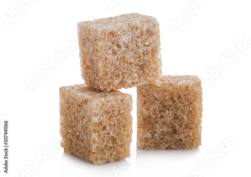 Close-Up shot of natural brown sugar cubes on white background.