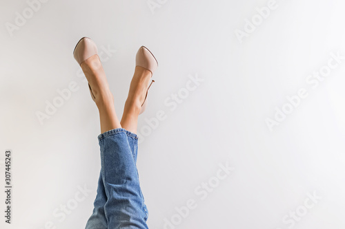 Photographie Female legs dressed in jeans and high heel shoes