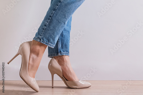 Woman's feet close-up wearing high heel shoes and jeans Fototapeta