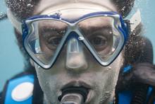 Primer Plano De La Cara De Un Buceador Dentro Del Mar Haciendo Burbujas Mientras Respira. Buceo Recreativo. Snorkel.
