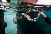 Couple Swimming Underwater Close To An Old Boat