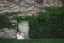 Woman In A White Dress Sitting In The Doorway Of An Ivy Covered Wall.