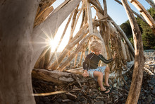 Young Boy Playing In Driftwood...