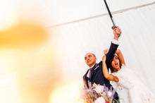 Exited Couple Of Newly Weds Raising A Sword To Cut The Wedding Cake