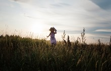 Girl Running Through A Meadow With A Paper Aeroplane At Sunset
