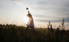 Girl Chasing A Paper Aeroplane In A Meadow At Sunset