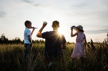 Father Playing With His Son And Daughter In A Meadow At Sunset