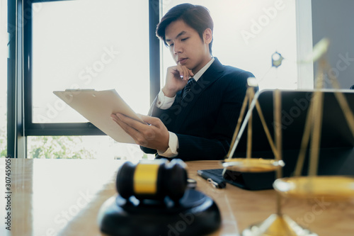 Photo Male lawyer in the office with brass scale.