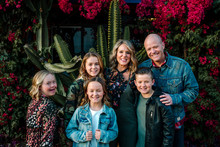 Laughing Family In Front Of Cactus And Flowering Red Bushes