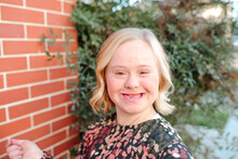 Happy Teen Girl With Down Syndrome Smiling By Brick Wall On Sunny Day