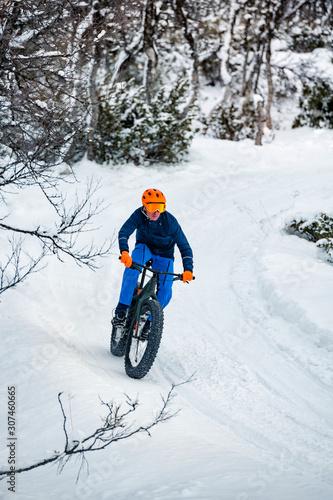Man cycling in winter landscape