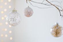 Christmas Balls On Golden Branch In White Interior