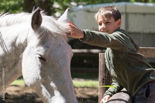 Fototapeta Niño con su mejor amigo, su caballo blanco.  obraz
