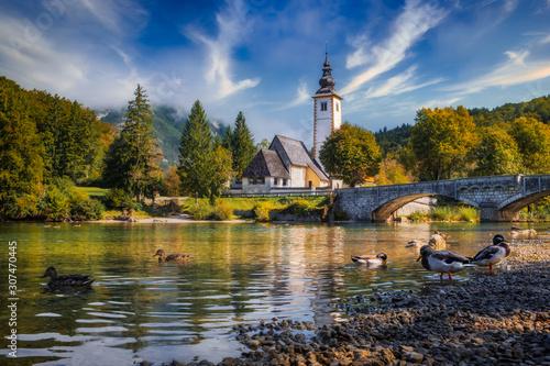 Photo Scenic view of Lake Bohinj church with beautiful colorful foliage, Slovenia