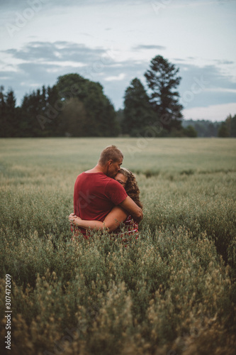 Couple hugging in meadow - 307472009