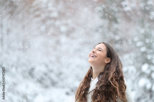 Happy girl breathing fresh air enjoying snow in winter