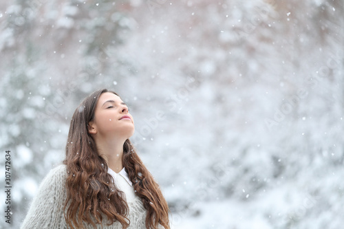 Relaxed girl breathing fresh air enjoying snow in winter - 307472634