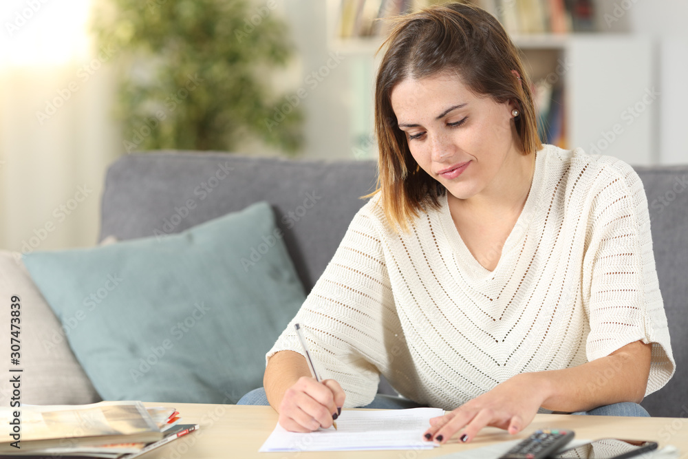Fototapeta Woman taking notes or filling form at home