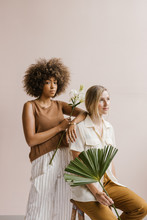 Two Young Stylish Women Posing Together Holding Florals And Tropical Leaves