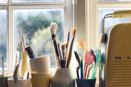 Obraz Paint brushes pens pencils and other art tools and equipment in a working art studio - fototapety do salonu