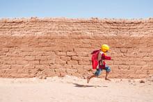 Ethnic Kid Running To School In Desert