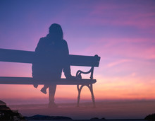 Silhouette Of Woman On Bench A...