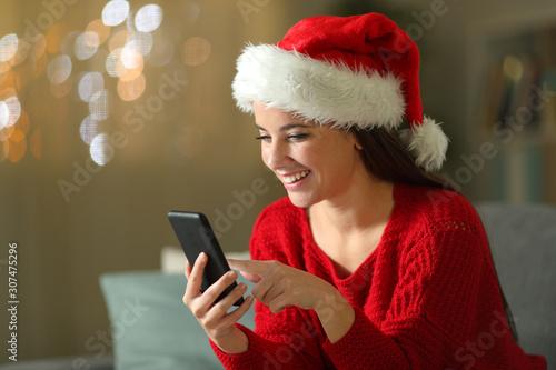 Happy woman checks mobile phone at christmas