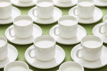 White Cups Of Milk On Green Backdrop