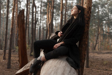Girl With Long Black Hair In A Dark Coat Sits And Poses On A Tree Trunk