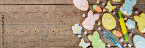 Fototapeta Happy easter background with pastel colored easter cookies - bunnies, eggs, flower, butterfly, Wooden rustic background, flatlay banner copy space obraz