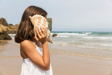 A Young Girl Listening To A Conch Shell On A Beach