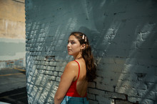 Young Woman Standing Next To Blue Painted Brick Wall