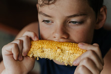 Close Up Of Boy Eating Sweet Corn
