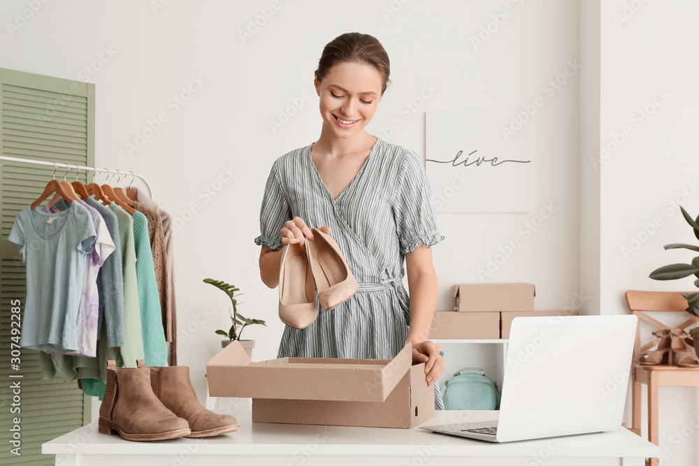 Fototapeta Young woman preparing parcel for client in office